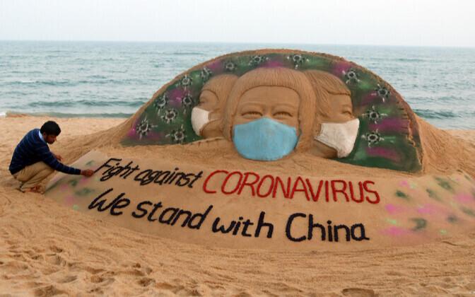 Koroonaviiruse-teemaline liivaskulptuur Indias.