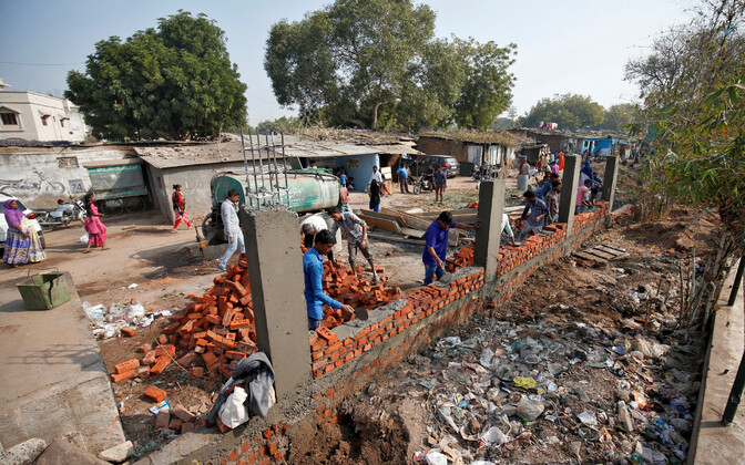 Müüri ehitamine slummi varjamiseks Ahmedabadis.