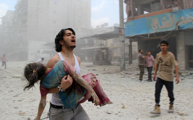 Haavatud tüdrukut kandev mees Süüria kodusõjas rängalt kannatada saanud Aleppo linnas.