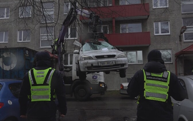 Municipal Police officials removing an abandoned vehicle in Tallinn.