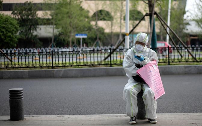 Kaitseülikonnas naine Wuhani tänavatel