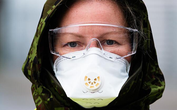 Inimene kaitsemaski ja -prillidega.