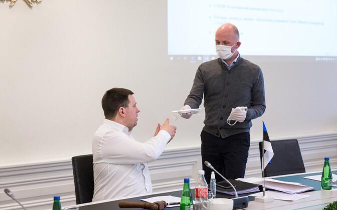 Riigisekretär Taimar Peterkop valitsuse 6. aprilli istungil peaminister Jüri Ratasele maski ulatamas