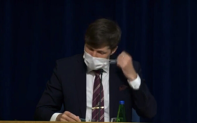Finance minister Martin Helme (EKRE) getting rid of his face mask before speaking at Thursday's press conference.