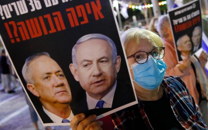 Meeleavaldaja Netnyahu ja Gantzi plakatiga.