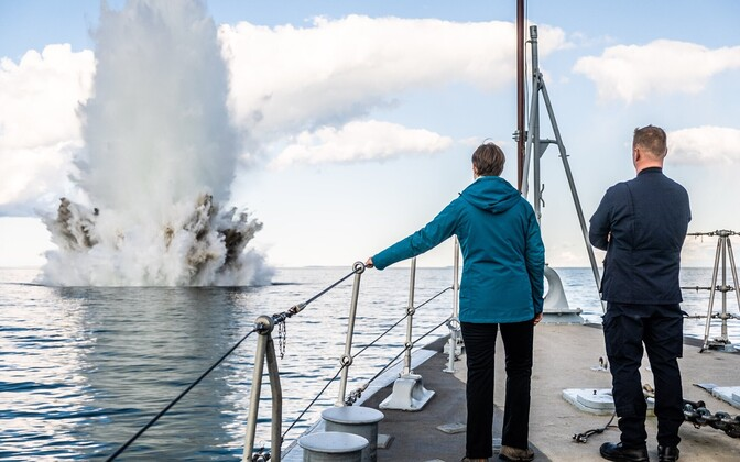 President Kersti Kaljulaid on board the Admiral Cowan, looking on at the plume of water thrown up by the destruction of a World War Two-era German sea mine.