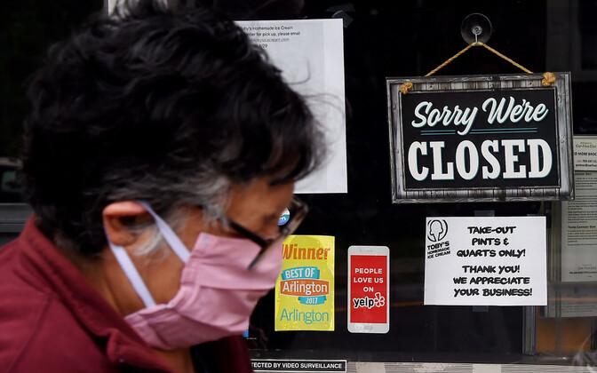Kaitsemaskis inimene koroonapandeemia tõttu suletud kaupluse ees.
