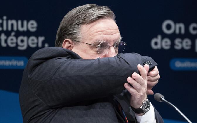 Kanada Quebeci peaminister Francois Legault köhimisel oma suud katmas.