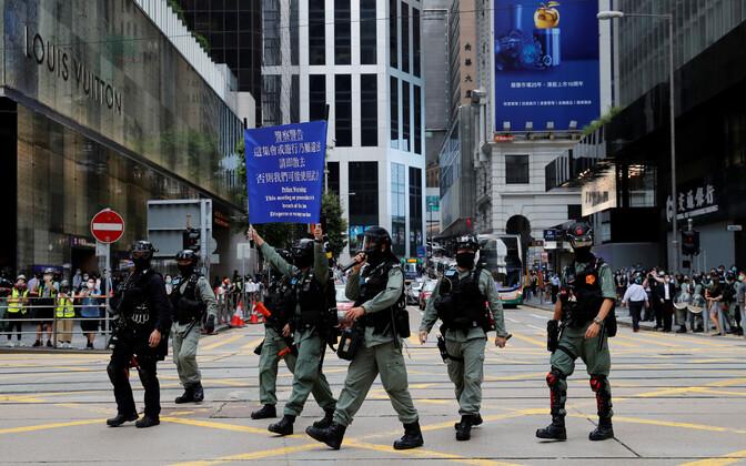Märulipolitseinikud Hongkongis inimesi kogunemise eest hoiatamas.