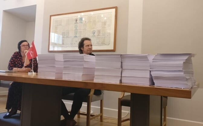 Indrek Saar and Katri Raik behind the blank papers representing the proposed 50,000 amends to the coalition's bill to remove the ERJK