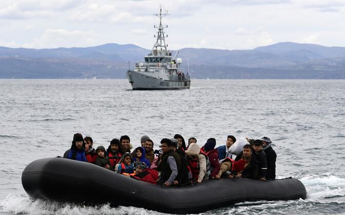 Paat Türgist Kreekasse suunduvate migrantidega, taustal Frontexi piirivalvelaev.
