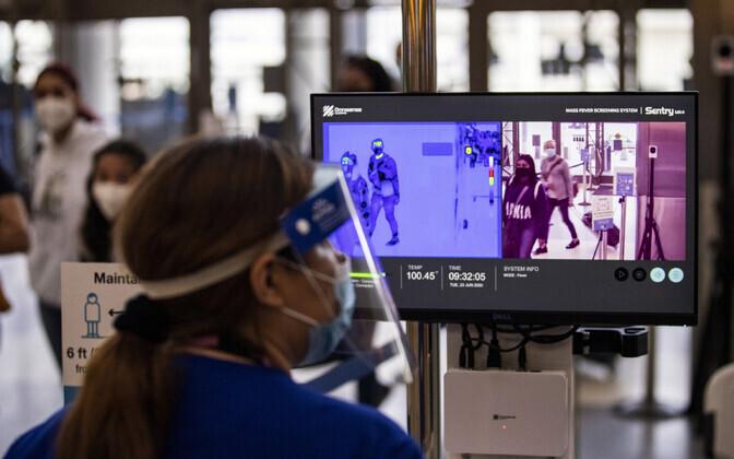 Meditsiinitöötaja jälgib lennujaama sisenevaid reisijaid.