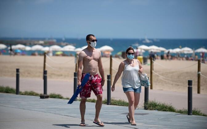 Maskidega inimesed Barcelona rannas.
