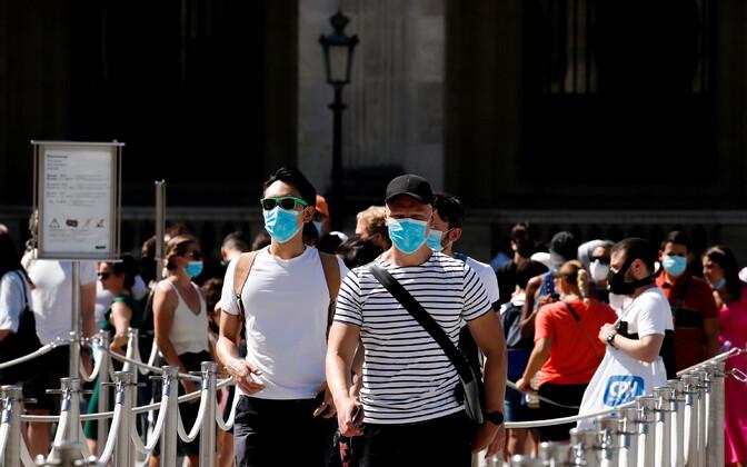 Maske kandvad inimesed Pariisis Louvre'i juures.