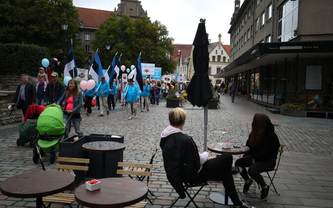 The vanguard of 'Elu Marss'' late August anti-abortion march approaches cafe goers in Tallinn's Old Town.