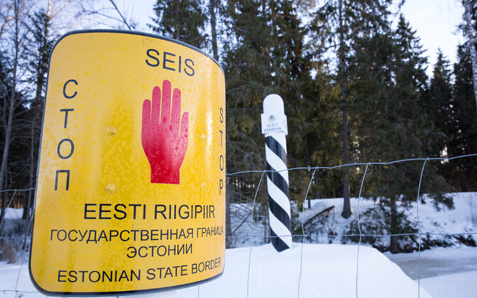 Estonian border marker and sign in three languages.