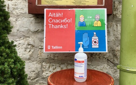 A social distancing sign and hand sanitizer outside a restaurant in Tallinn's Old Town.