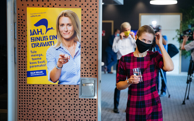 Chairman of the Reform Party Kaja Kallas wearing a mask and standing next to a campaign poster on September 25.