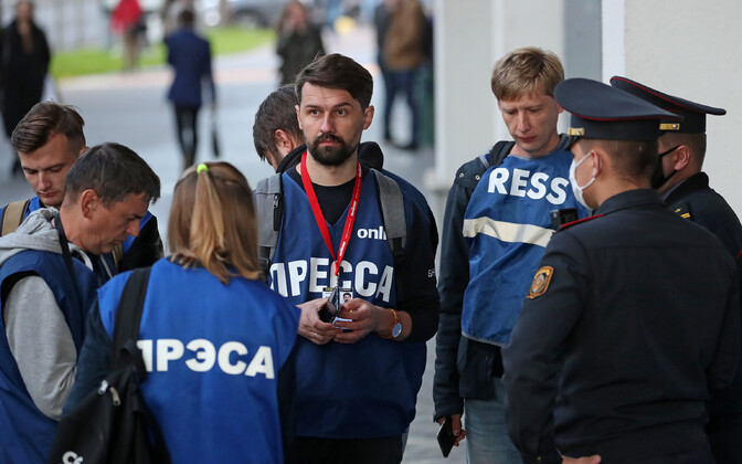 Ajakirjanikud meeleavaldusel Valgevene miilitsatega rääkimas.