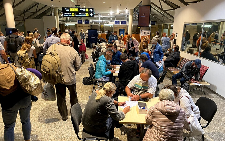 Travellers at Tallinn Aiport filling in a coronavirus questionnaire.