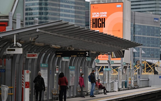 Inimesed Londonis raudteepeatuses, taustal kõrgest koroonaohust teavitav silt.