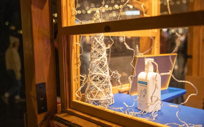 Vaateaken jõulukaunistuste ja desovahendi pudeliga Tallinna vanalinnas.