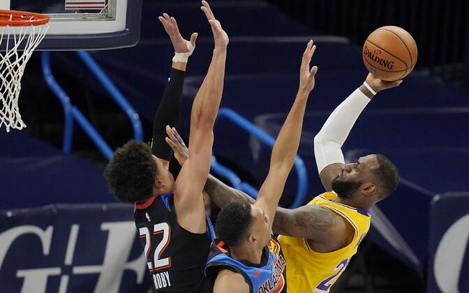 LeBron James viskel, Isaiah Roby (22) ja Darius Bazley püüavad teda takistada