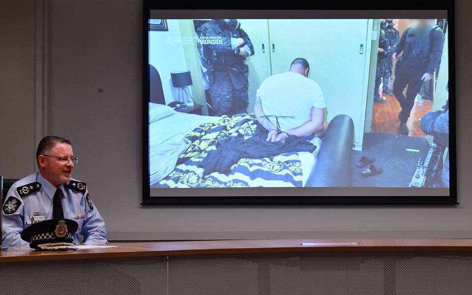 Сотрудник Австралийской федеральной полиции показывает на пресс-конференции видео задержания членов преступных организаций.