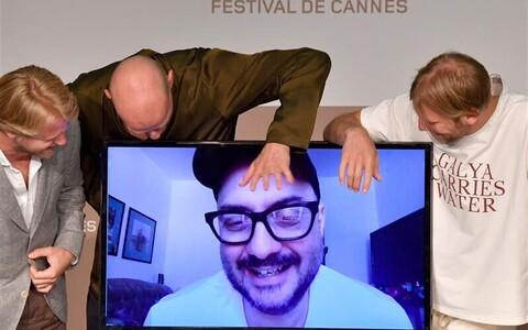 """Näitlejad Juri Kolokolnikov ja Ivan Dorn ning produtsent Ilja Stewart lehvitamas sunniviisiliselt Venemaal viibivale Kirill Serebrennikovile Cannes'i filmifestivalil, """"Petrovid gripi küüsis"""" pressikonverentsil."""