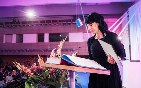 Siret Malmberg doktorite promoveerimisel andmas allkirja auraamatusse.